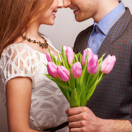 couple in love with a bouquet of tulips are close to each other Standard-Bild