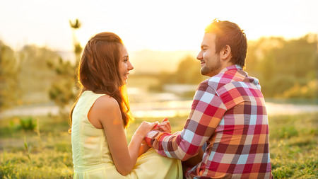 back view of young happy couple sitting on river at sunset. concept of Valentines Day