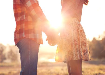 romance: Jeune couple dans l'amour marchant dans le parc de l'automne se tenant la main en regardant dans le coucher du soleil