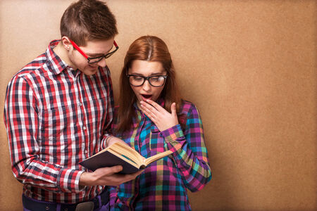 young couple in clothes and stylish hipster glasses reading a book. studio shot photo