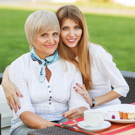adult mother and daughter drinking tea or coffee and talking outdoors  Mothers day  Stock Photo