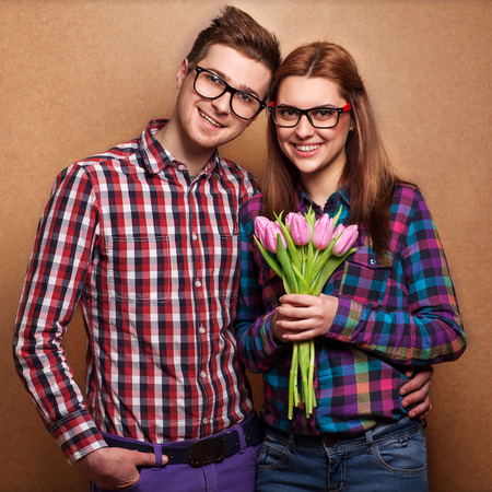 Young couple in love make a heart and hands are holding a bouquet of tulips. The concept of Valentine's Day photo