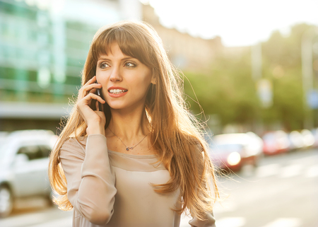 Sophisticated businesswoman in dress talking on the phone. photo