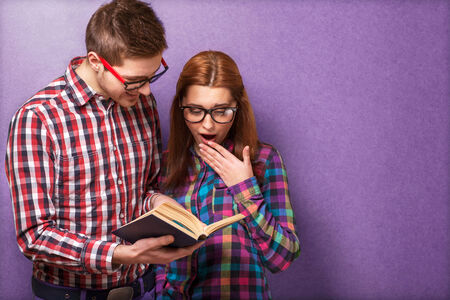 young couple in clothes and stylish hipster glasses reading a book  studio shot photo
