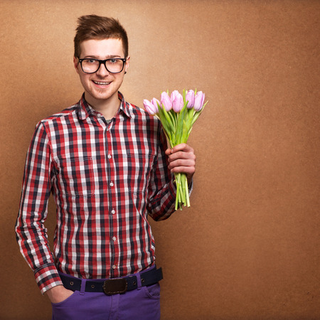 suitor: A young romantic man holding a bouquet of flowers isolated on white background  Stock Photo