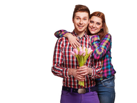 Young couple in loveholding a bouquet of tulips  The concept of Valentine photo