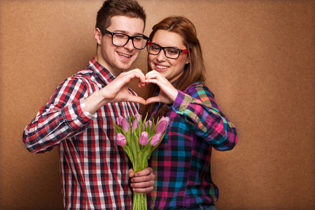 Young couple in love make a heart and hands are holding a bouquet of tulips. The concept of Valentines Day  photo
