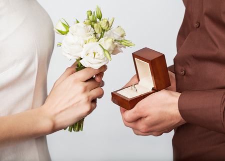 Wedding couple holding ring box and a bouquet of flowers photo