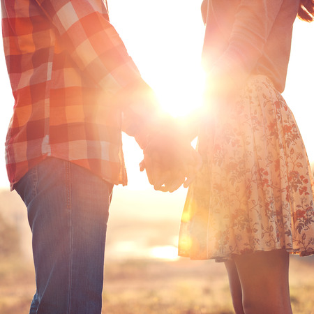 boy romantic: Young couple in love walking in the autumn park holding hands looking in the sunset