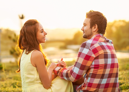 back view of young happy couple sitting on river at sunset photo