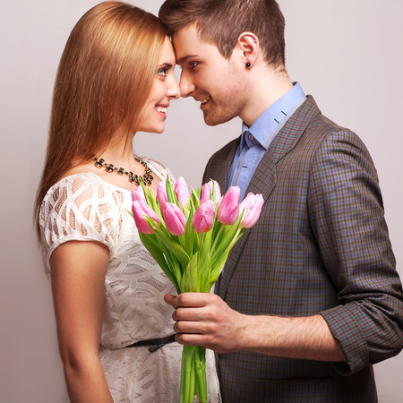 couple in love with a bouquet of tulips are close to each other  Focus on the tulips
