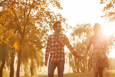 couple holding hands: Young couple in love walking in the autumn park holding hands