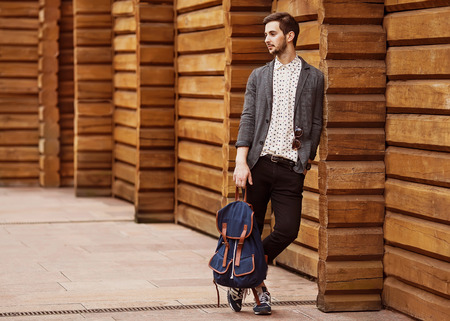Portrait of young beautiful fashionable man against wooden wall  Hipster style guy
