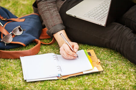young fashion male student sitting on grass in park and holding a laptop photo
