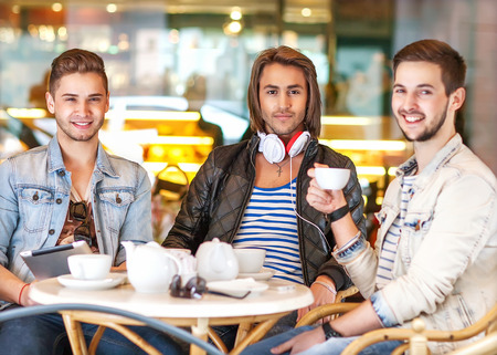 Three young men students in cafe photo