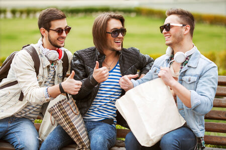 fashion young guys consider shopping with shopping bags in their hands photo