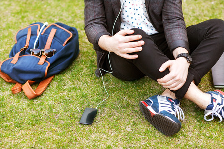 fashion young guys consider shopping with shopping bags in their hands. the background green park.  Stock Photo
