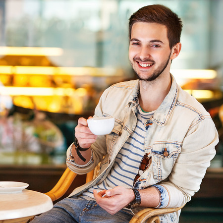 Young fashion man with beard drinking espresso coffee in the city cafe during lunch time photo