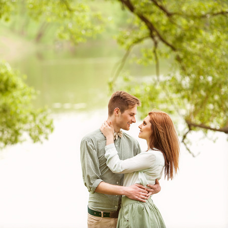 walk in: Couple in love walk near the riverr, smiling . Valentines Day Stock Photo