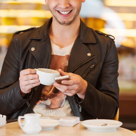 young hipster guy sitting in a cafe chatting and drinking coffee smiling photo