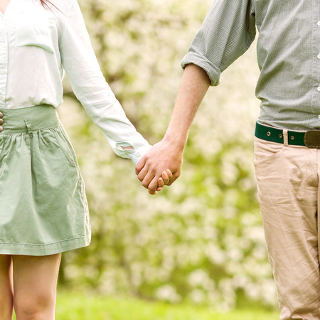 Young couple in love walking in the spring park holding hands looking in the sunset