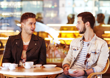 Two young hipster guy sitting in a cafe chatting and drinking coffee smiling photo