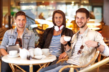 chicos inconformista jóvenes sentados en una cafetería charlando y bebiendo café sonriendo Foto de archivo