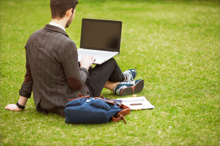 ultrabook: young fashion male student sitting on grass in park and holding a laptop