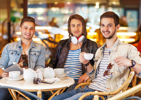 young hipster guys sitting in a cafe chatting and drinking coffee smiling and using tablet computer in cafe photo