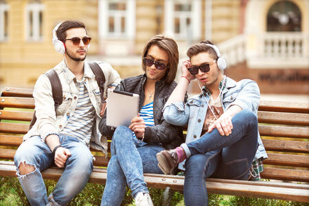 fashion boys sit in the park listening to music and holding a tablet photo