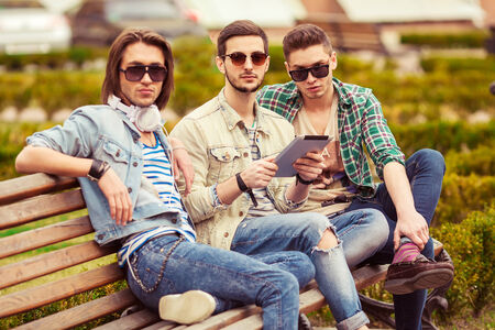 fashion hipster boys sit in the park listening to music and holding a tablet photo