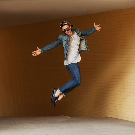 teenage hipster man jumping on the street photo
