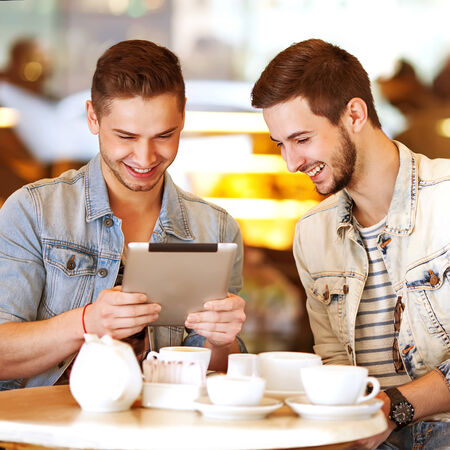Two young men  students using tablet computer in cafe photo