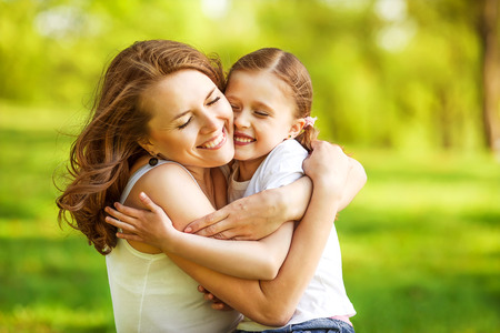 hugging: mother and daughter hugging in love playing in the park Stock Photo