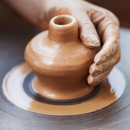 alfarero: Manos Potter decisiones en arcilla en el torno de alfarer�a. Potter hace en la olla de barro, alfarer�a, rueda. Foto de archivo