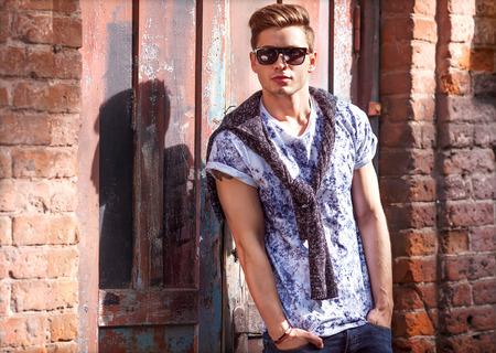 modelos hombres: Chico estilo inconformista. Moda hombre de pie cerca de una puerta de madera Foto de archivo