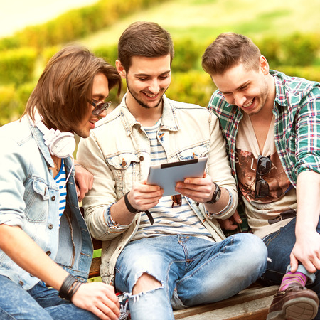 Three young men friends using tablet computer in park photo