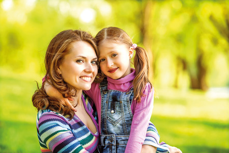 mother and daughter hugging in love playing in the park photo