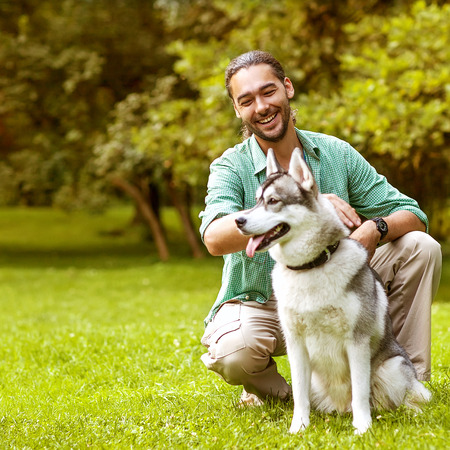 Man and Husky dog walk in the park  He keeps the dog on the leash Stock Photo - 30479739