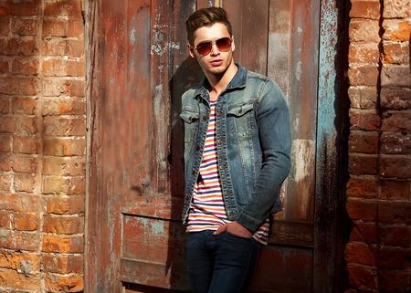 Hipster stijl vent. Mode man staande in de buurt van een houten deur