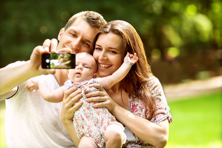 Family with baby In Park  taking selfie by mobile phone Foto de archivo