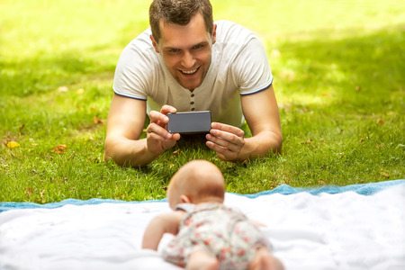 Father with baby In Park  taking selfie by mobile phone photo