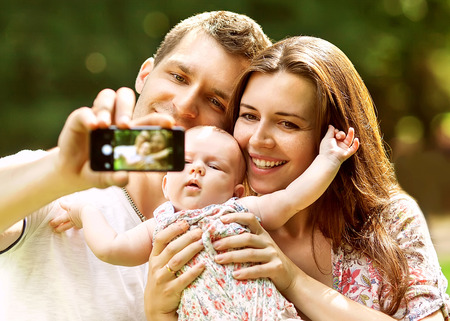 Family with baby In Park  taking selfie by mobile phone Standard-Bild