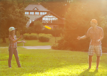 � father and daughter spend a fun time at the park playing flying plate photo