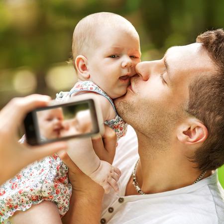 b�b� filles: En famille avec b�b� dans le parc prenant selfie par t�l�phone mobile