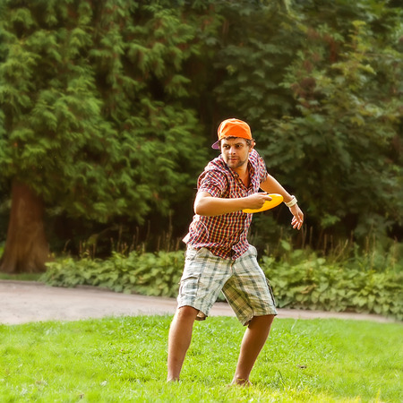 man playing in the park with a flying plate  photo