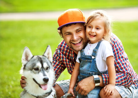 father and  daughter playing in the park in love with Dog Husky photo