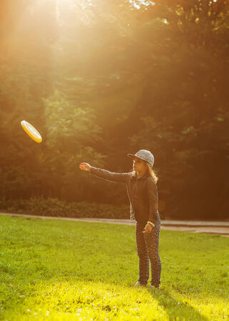 disc golf: girl spend a fun time at the park playing tossing plate Stock Photo