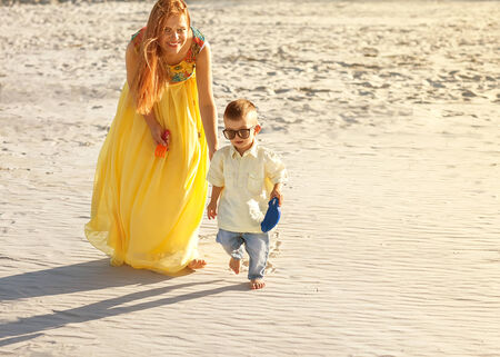 Happy mother and son on the beach sunset photo