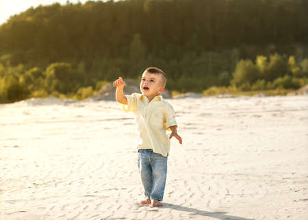 little boy of two walks on the sand in the mountains photo